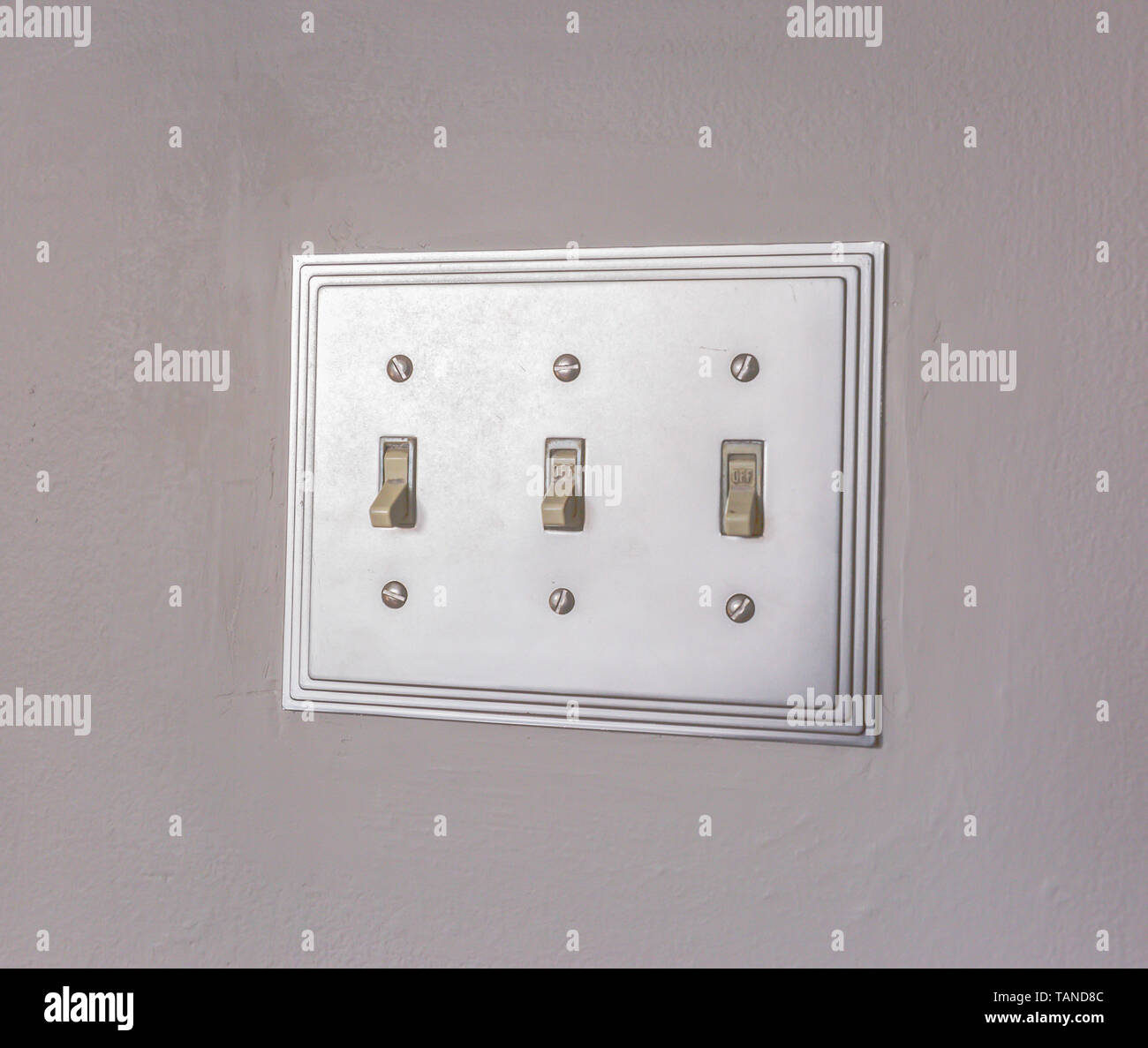 Close up of the electrical light switch against the white wall of a house. The vertical flip toggle light switches is in off mode. - Stock Image