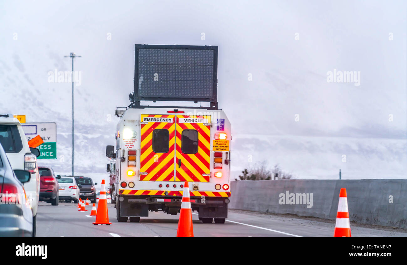 Back view of an emergency vehicle on the road with traffic cones and cars. An unlit LED arrow board is mounted on the roof of the vehicle. - Stock Image
