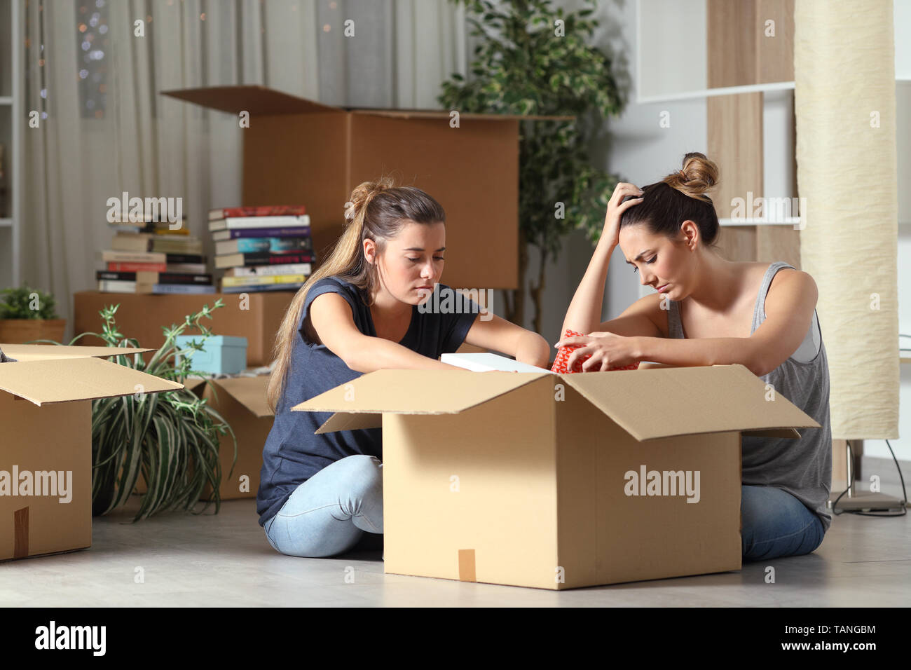 Sad evicted roommates boxing belongings moving home sititng on the floor - Stock Image