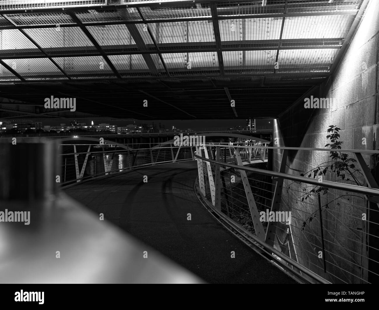 Perspective view of pedestrian overpass above the River Thames with steel fence and guard rails at night. Black and white image. Bridges and the river - Stock Image
