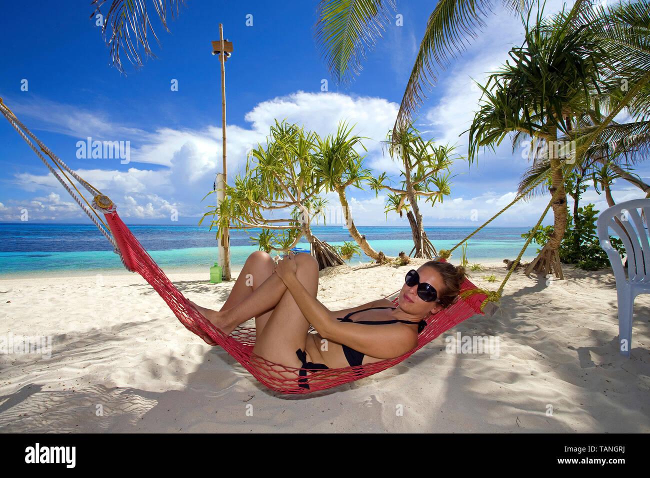 Girl relaxing on a hammock at Bounty beach, Malapascua island, Cebu, Philippines - Stock Image