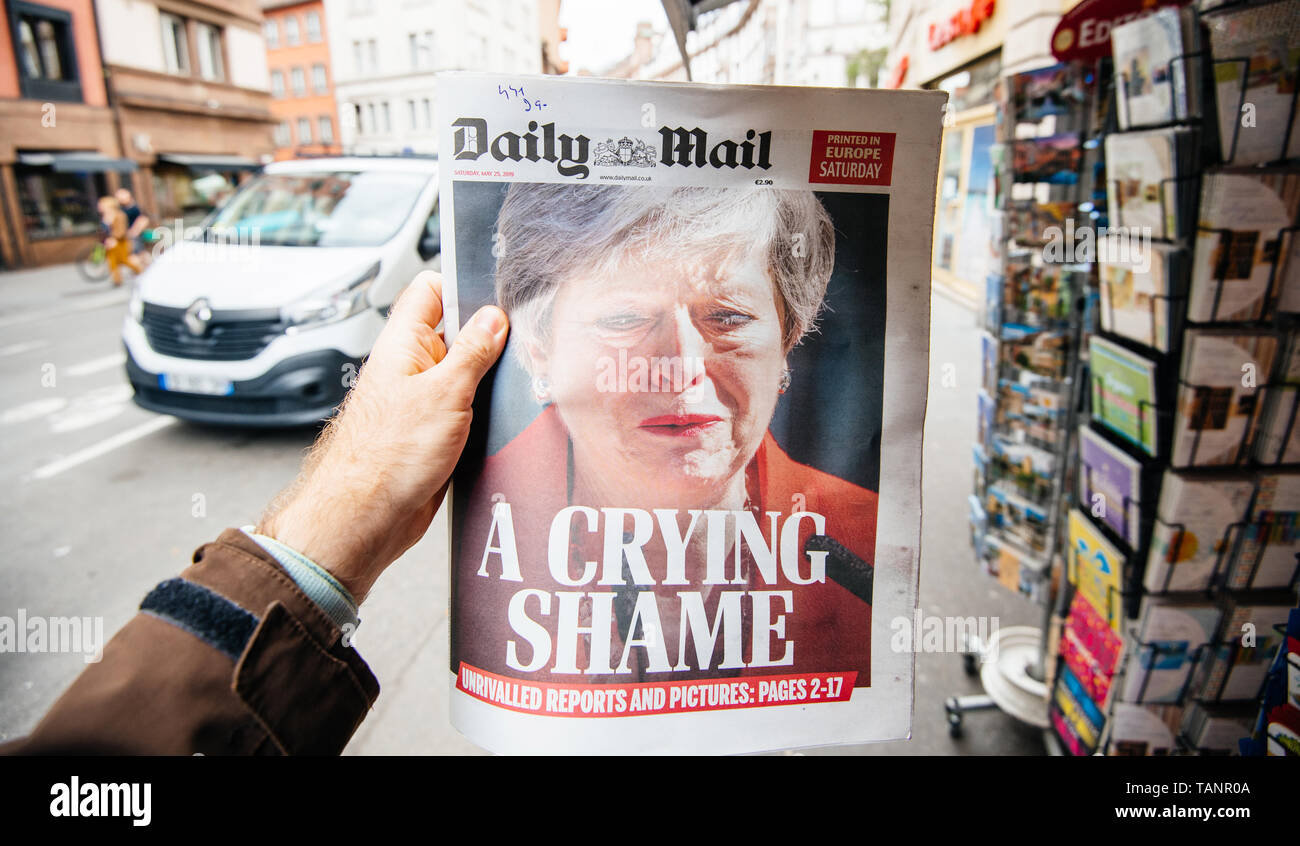 Strasbourg, France - May 27, 2019: Man holding buying newspaper front page on street press kiosk newsstand with the Theresa May crying announcing resignation - Stock Image