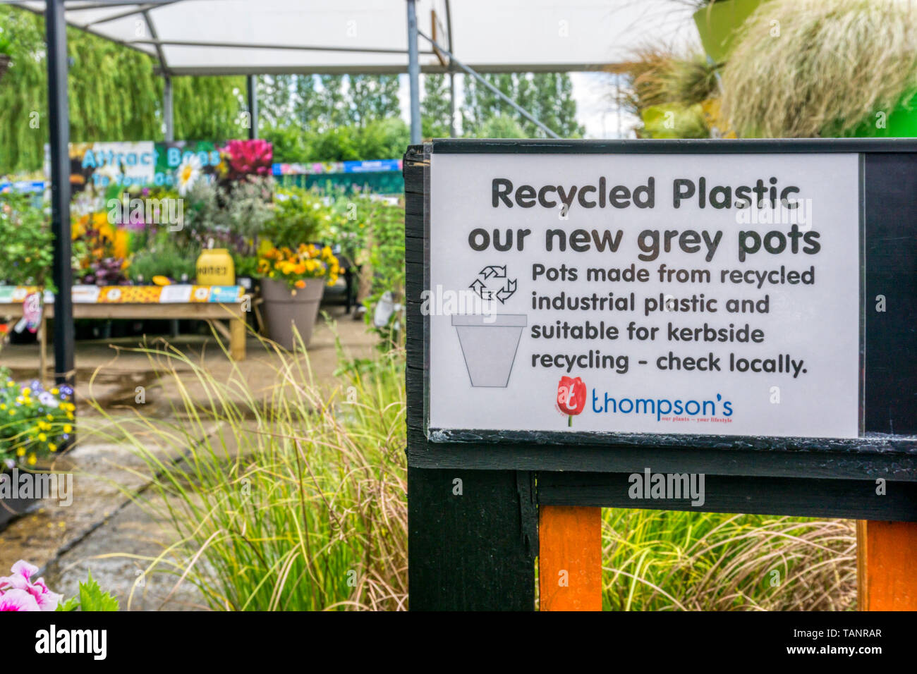 Sign at a garden centre advertises recyclable grey plastic flower pots made from recycled industrial plastic which can be recycled themselves. - Stock Image