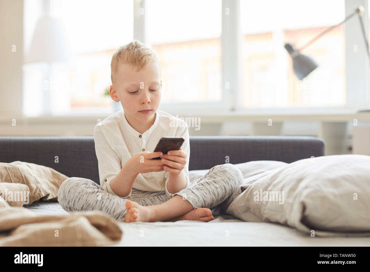 Serious concentrated blond-haired boy in homewear sitting with crossed legs on bed and using smartphone in morning - Stock Image