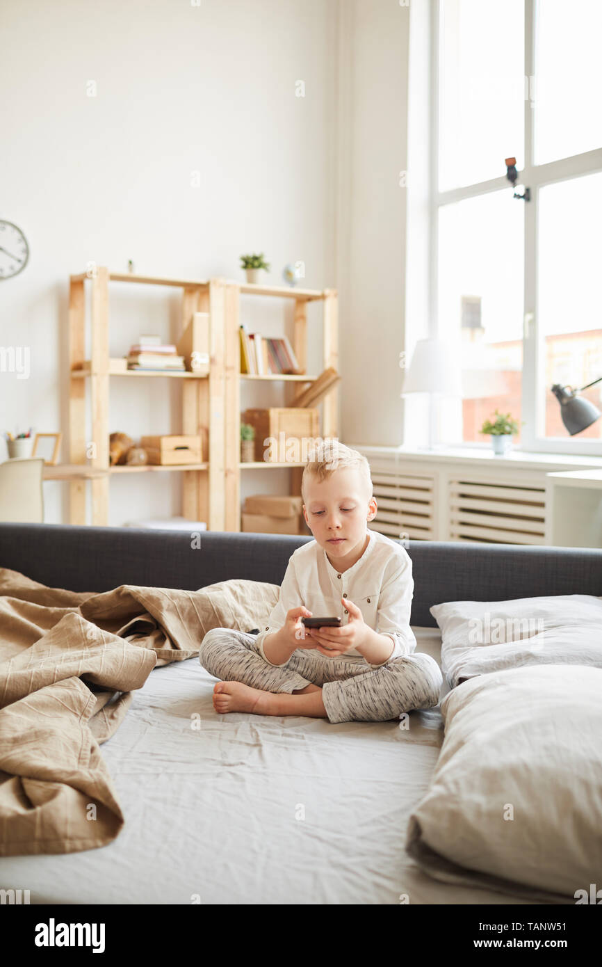 Serious gadget-addicted kid sitting with crossed legs on sofa bed and using modern device while surfing net at home - Stock Image