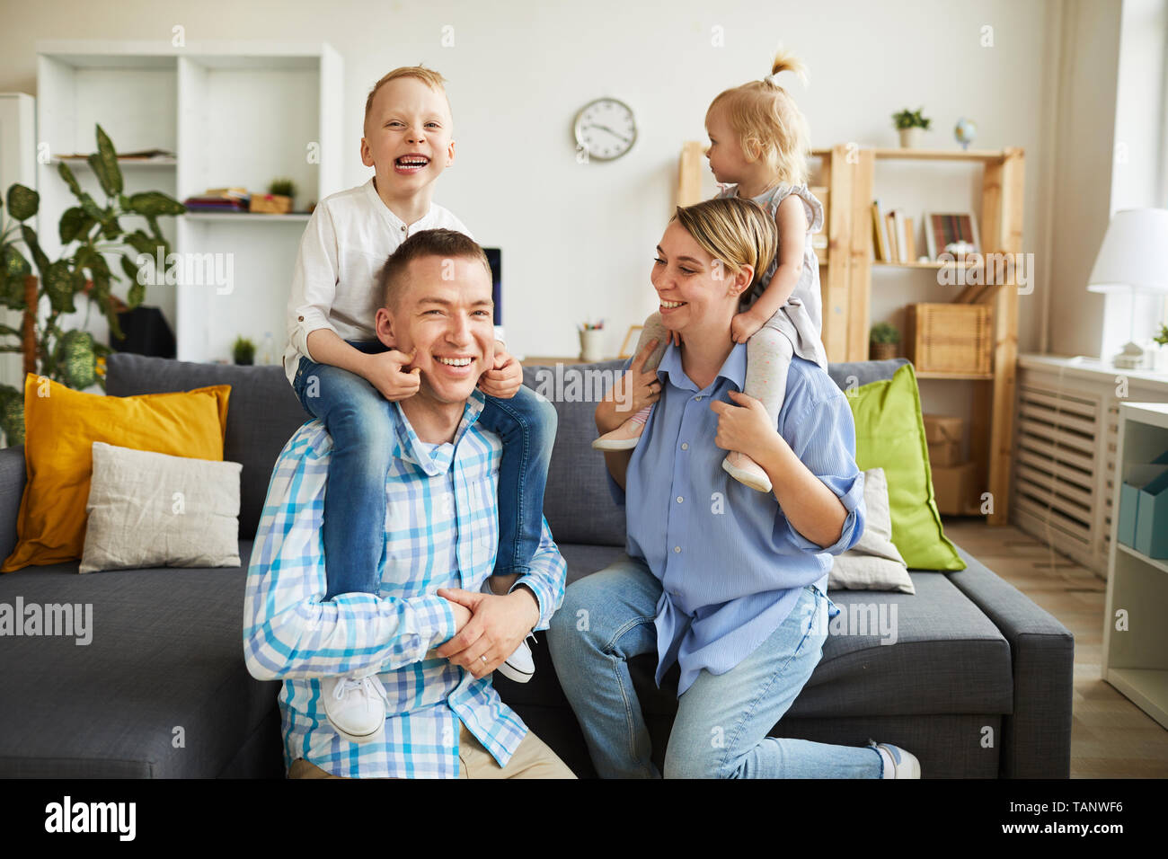Cheerful emotional kids grimacing and riding parents necks while having fun together in living room - Stock Image