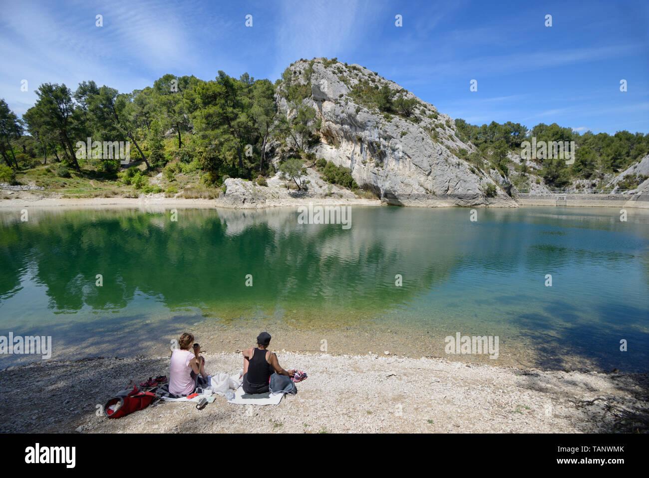 A Couple Picnicking at Peiroou Lake, Lac de Peirou, or Glanum Barrage in the Alpilles Hills near Glanum, Saint Remy-de-Provence Provence France - Stock Image