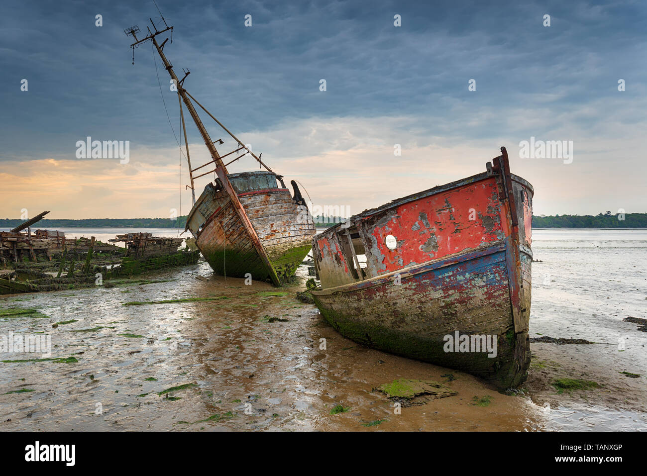 Old boat wrecks under a stormy sky on the River Orwell at Pin Mill on the Suffolk coast Stock Photo