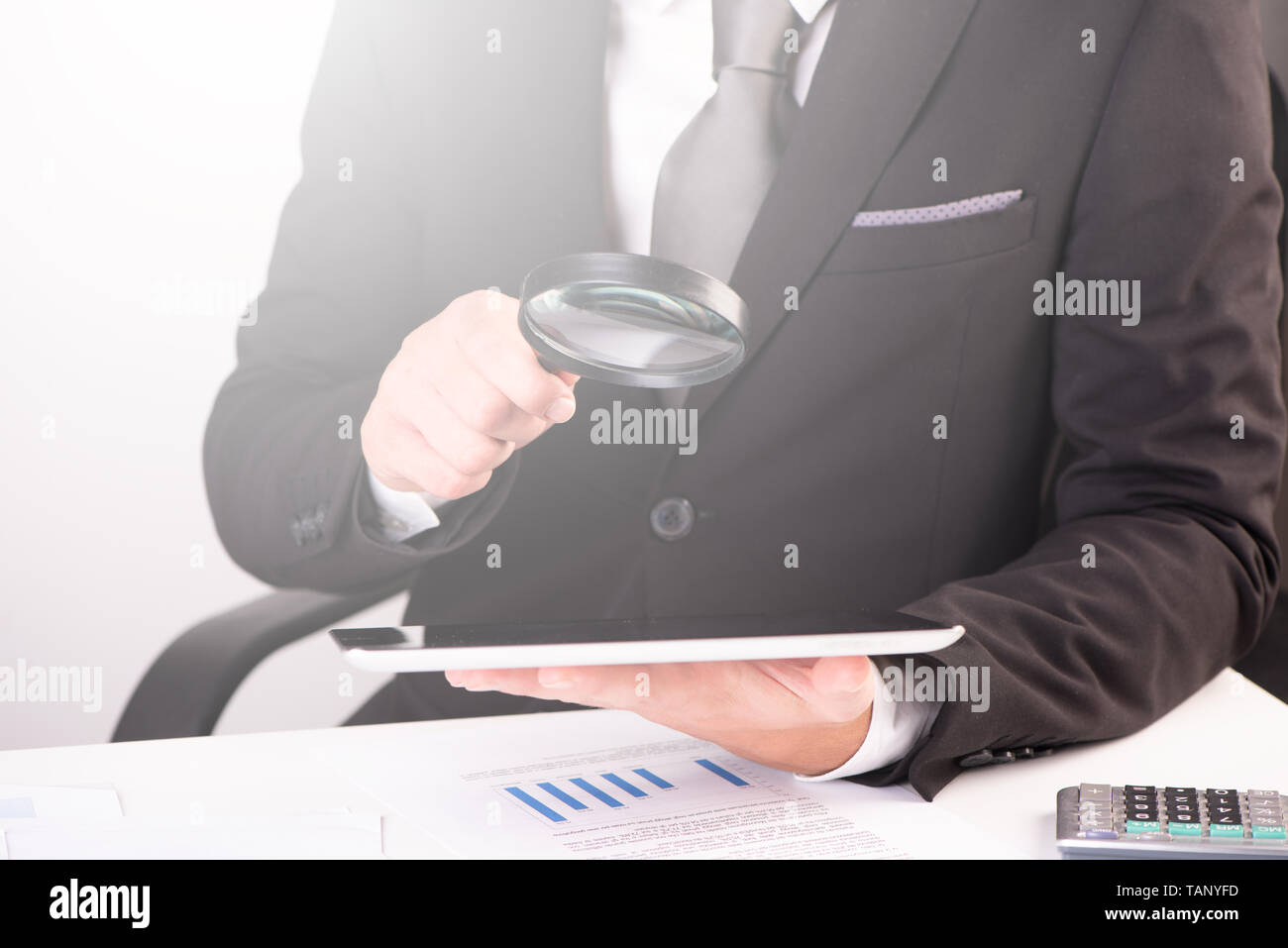 Businessman holding magnifying glass and digital tablet close up Stock Photo