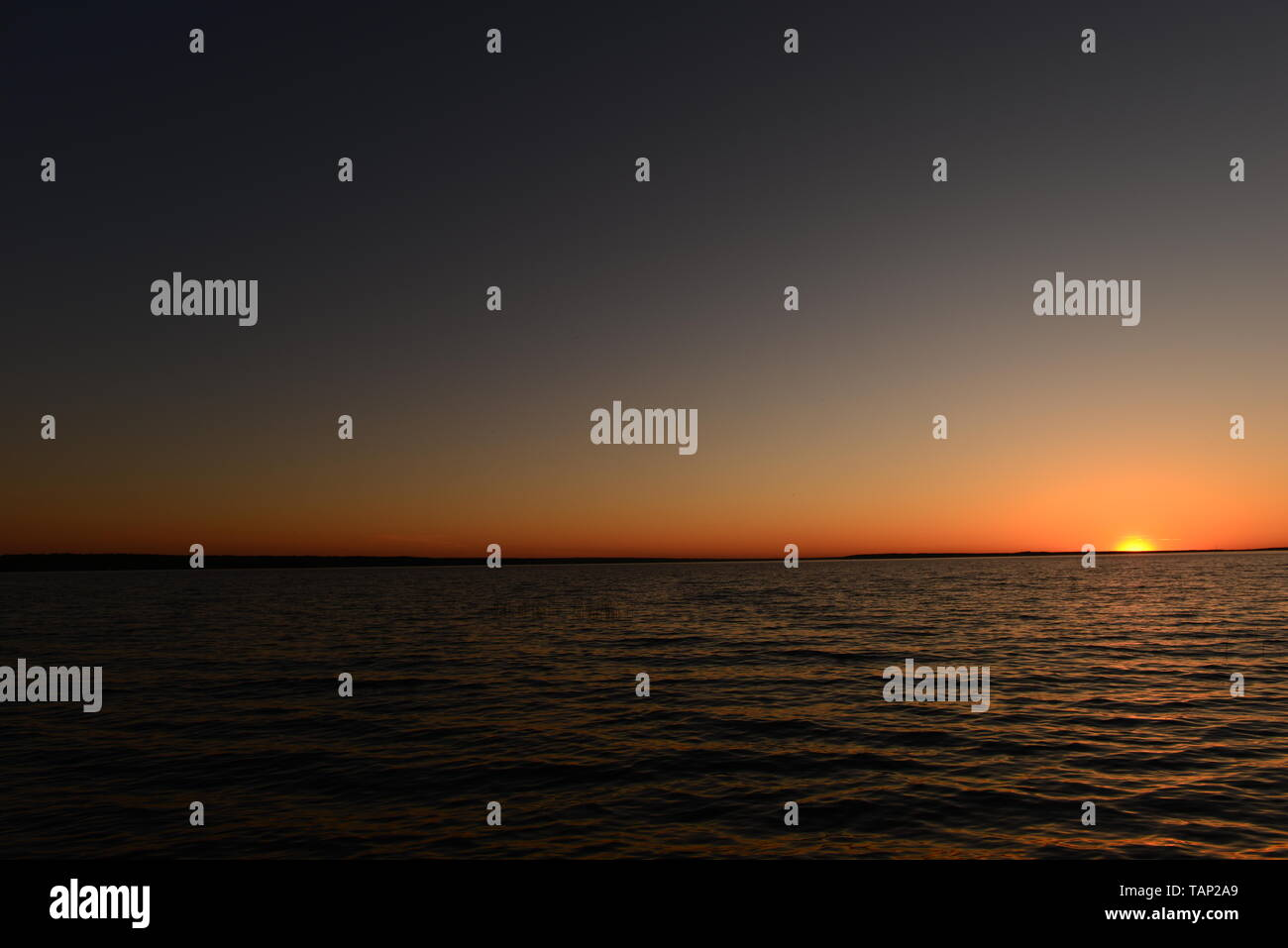 Dark sky in the glow of sunlight in a semicircle around the sun on the horizon above the water of the lake at sunset - Stock Image