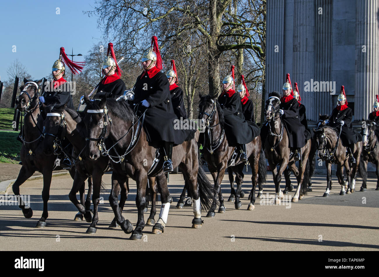 LONDON, UK - JANUARY 28, 2016:  Cavalry soldiers from the Blues and Royals regiment riding through Wellington Arch at Hyde Park Corner.  Part of the H - Stock Image