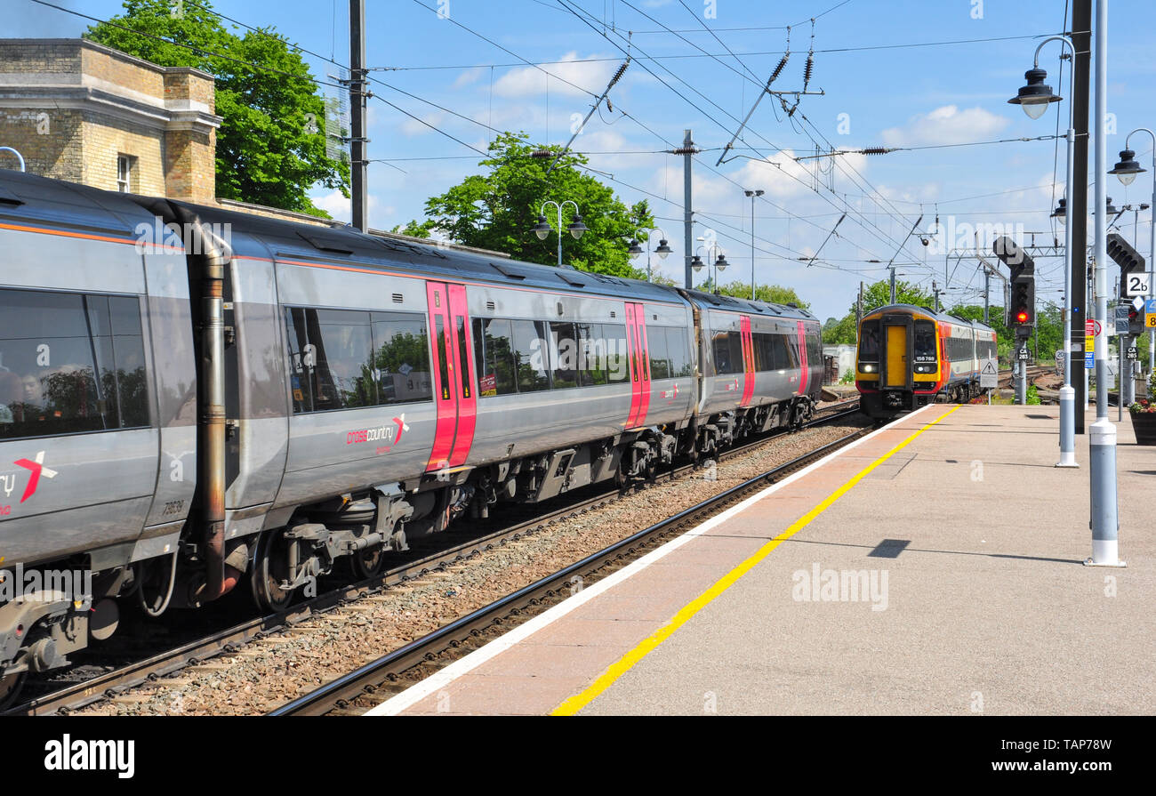 East Midlands class 158 DMU pulls into platform 2 while a Cross Country class 170 'Turbostar' train stands alongside in platform 1 at Ely, Cambridgesh - Stock Image