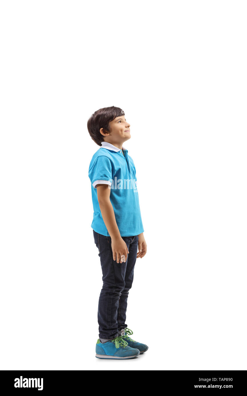 Full length profile shot of a smiling boy standing and looking upwards isolated on white background - Stock Image