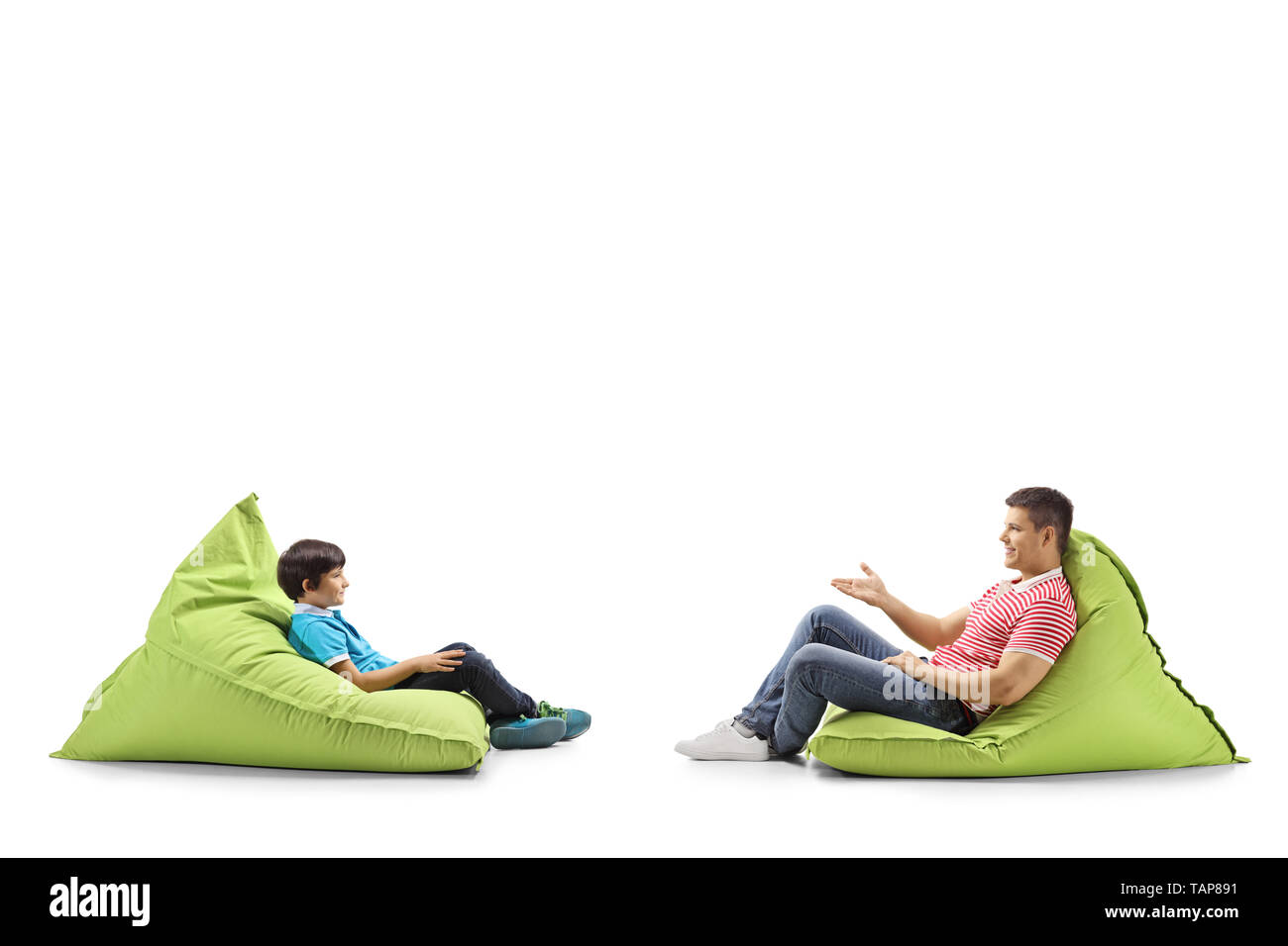 Full length profile shot of a father and son sitting on green bean bags and talking isolated on white background - Stock Image