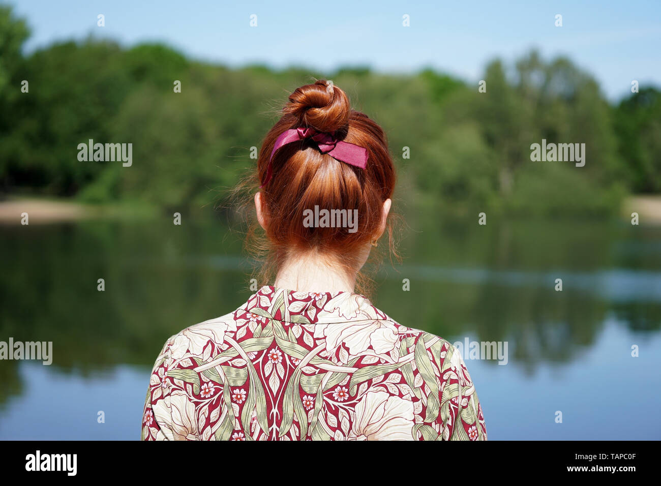 back view of unrecognizable young woman with floral dress and red hair bun looking at lake in solitude Stock Photo