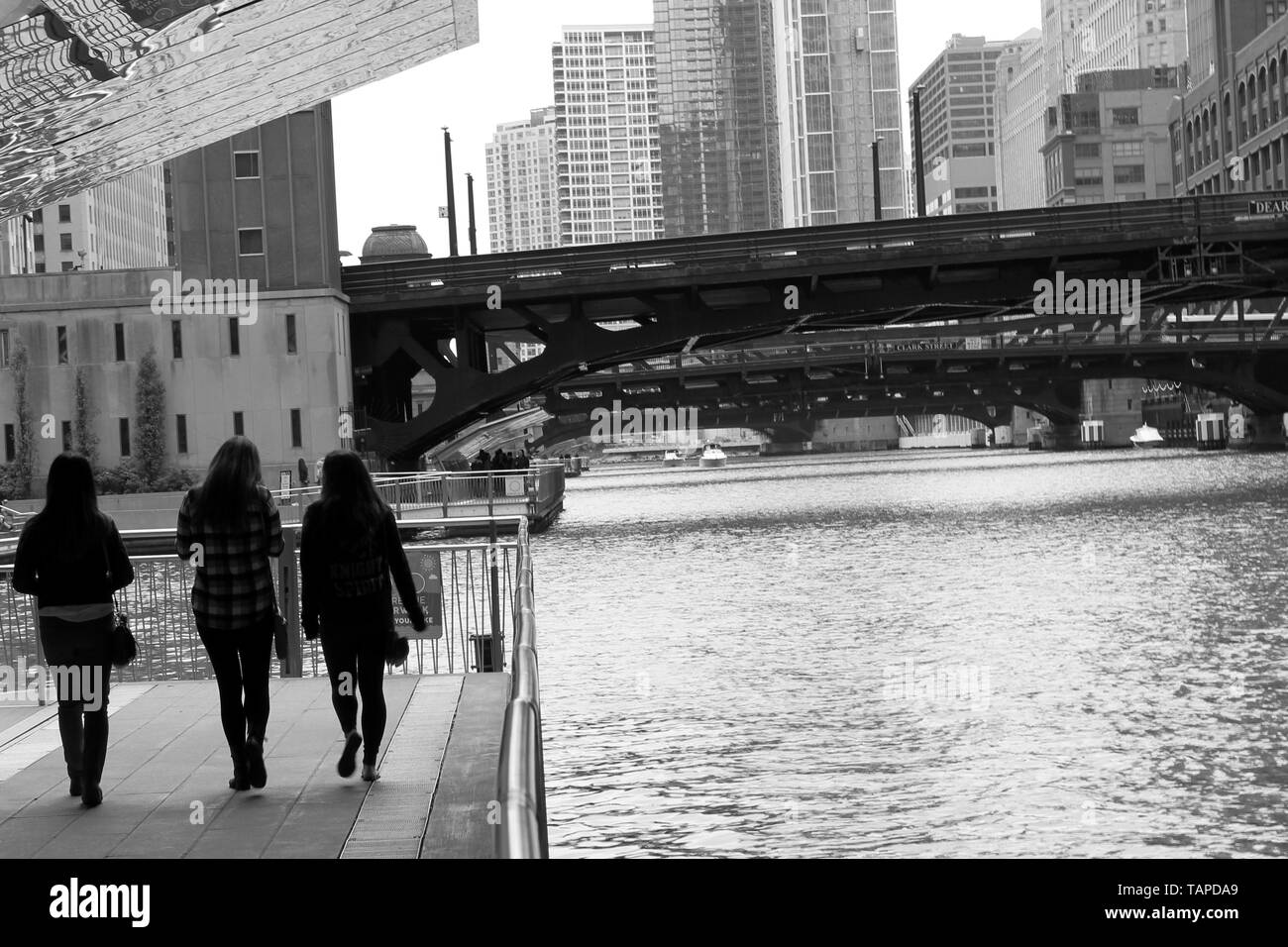 Three people walking on the Riverwalk on the Chicago River downtown in the Loop, Chicago, Illinois, USA - Stock Image