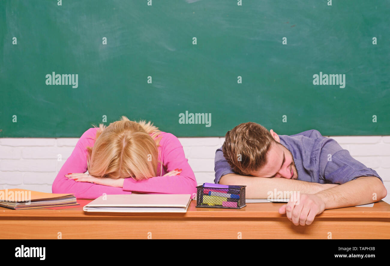 Feeling bored. Studying in college or university. Apply for free program. Couple friends student studying university. Student life issues. Guy and girl tired or lazy student lean on desk in classroom. - Stock Image