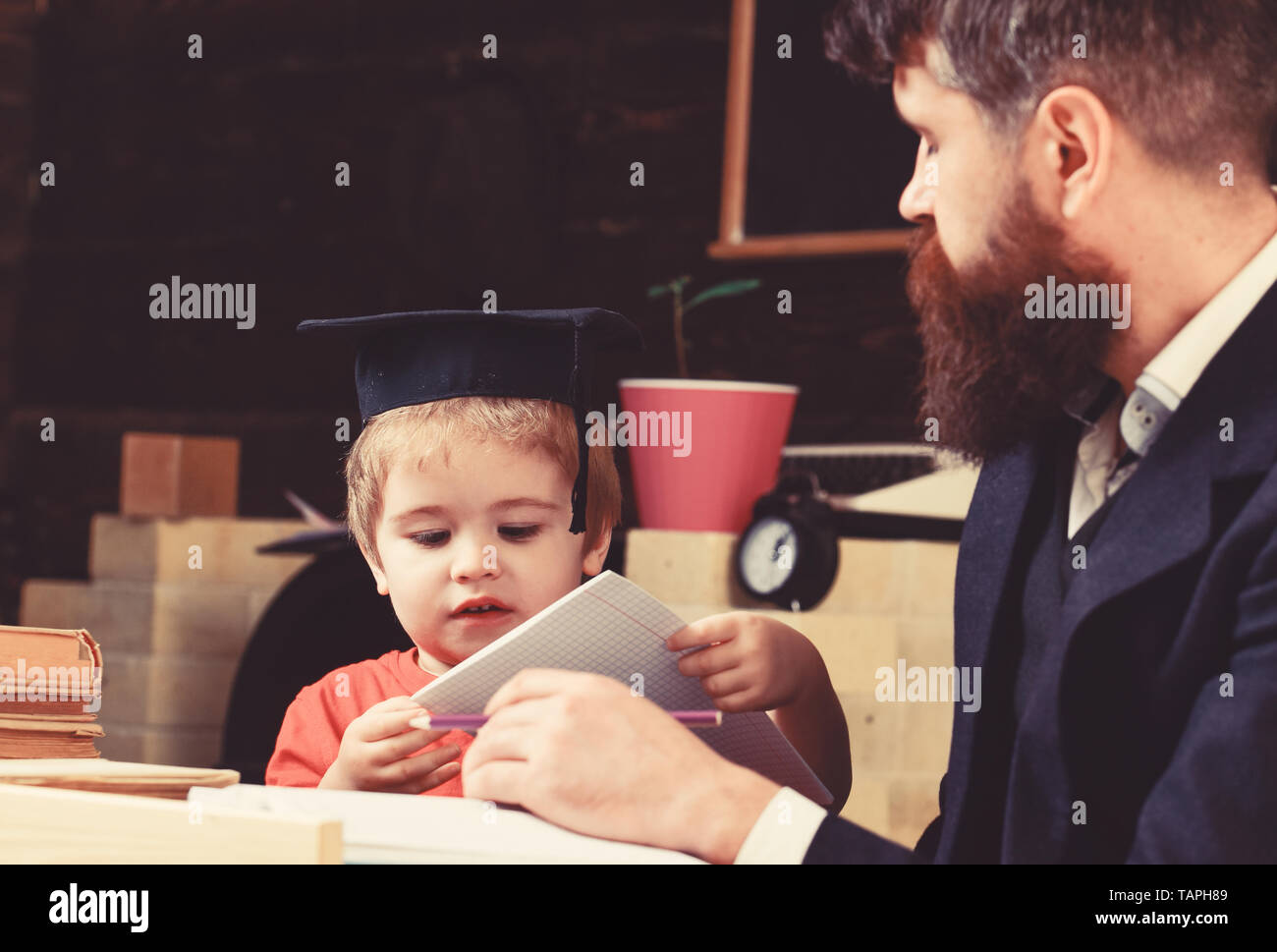 Elementary education concept. Kid studies with teacher, listening with attention. Teacher and pupil in mortarboard, chalkboard on background. Father teaches son elementary knowledge, discuss, explain. - Stock Image