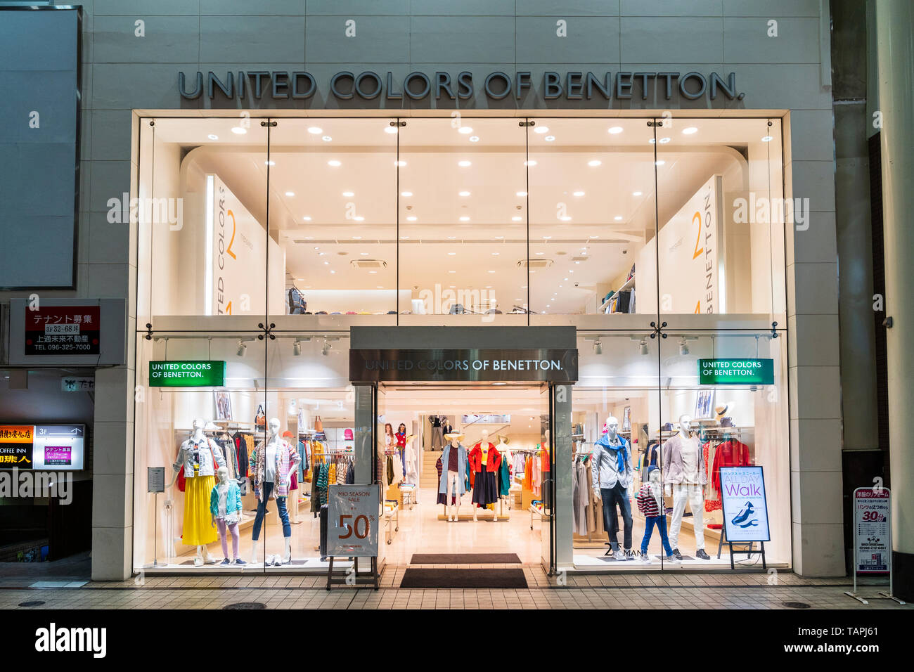 Benetton fashionable clothing store in Shimotori shopping arcade, Kumamoto, Japan. Night shot of exterior of open shop with 50% sale sign by entrance. - Stock Image
