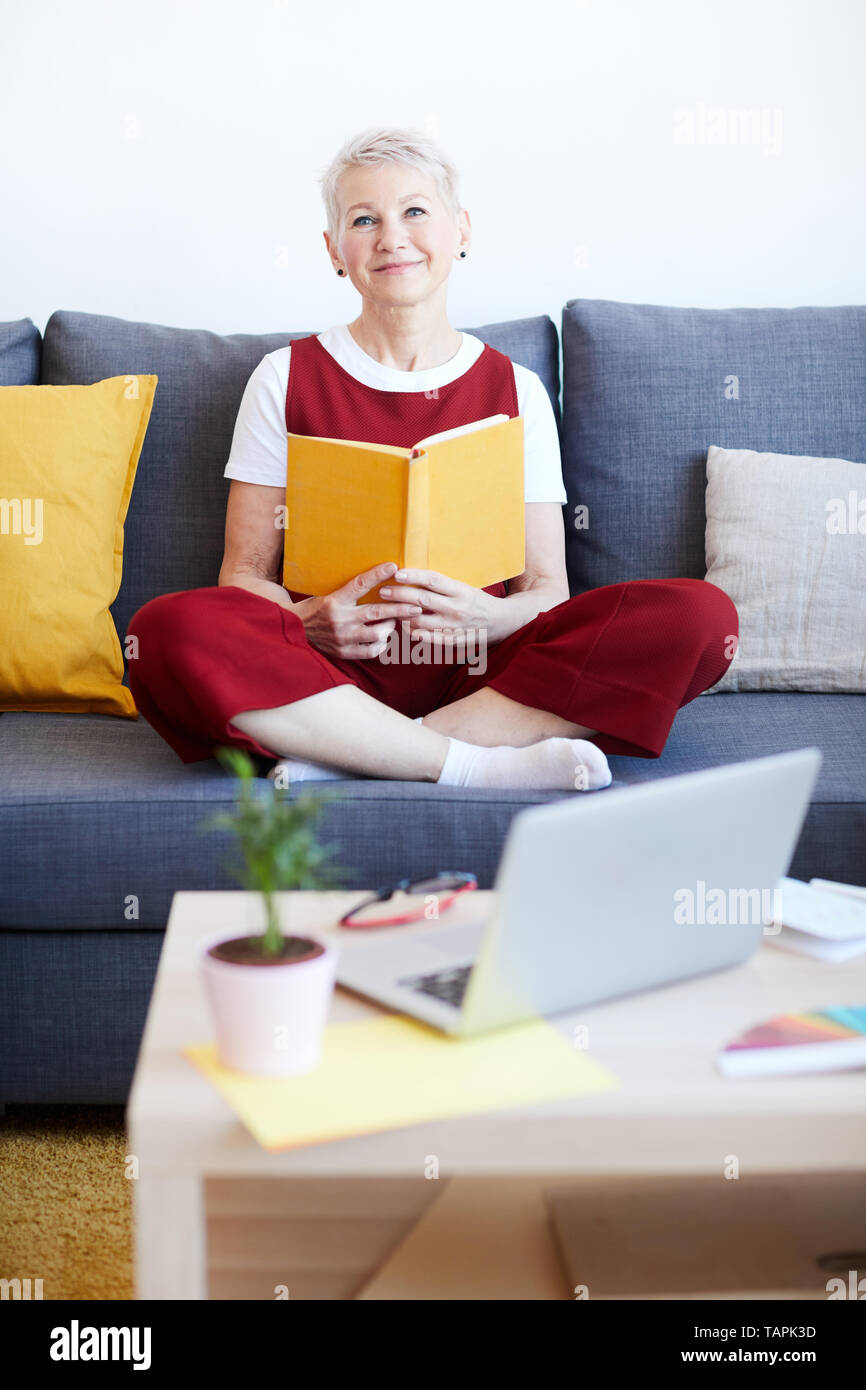 Happy blonde female in casualwear relaxing on couch with book while spending weekend at home - Stock Image