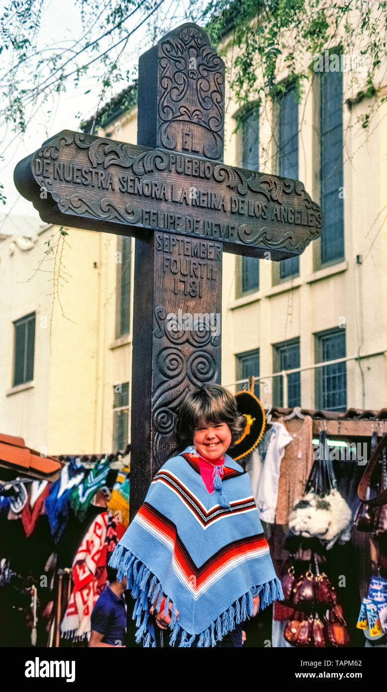 A smiling young girl in a souvenir serape poses in front of a huge wooden cross that commemorates the 1781 founding of the El Pueblo de Los Angeles, now the City of Los Angeles, California, USA. The inscription in Spanish, El Pueblo de Nuestra Señora la Reina de los Ángeles, translates as The Town of Our Lady the Queen of the Angels. Also inscribed is the name of the town founder and governor of Spanish California, Felipe de Neve. The cross stands at the south end of Olvera Street, which has been a Mexican marketplace since 1930 and attracts visitors with vendor stalls, shops and dining spots. - Stock Image
