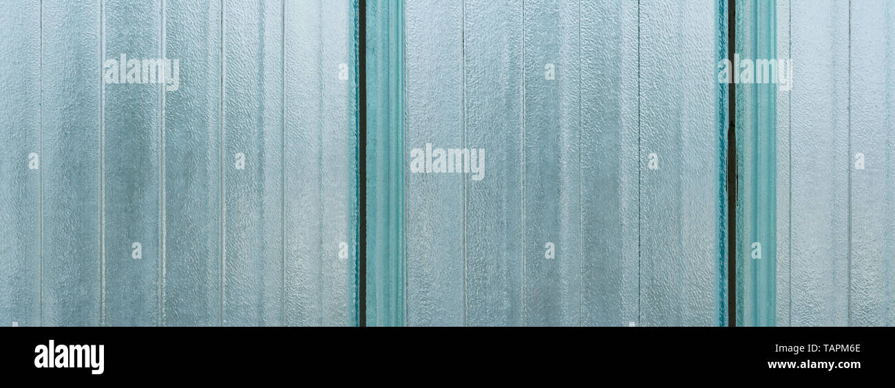 Opaque striped glass wall blocks. Architecture detail. Wide-angle background from vertical strips. Big translucent brick. Abstract blue grainy texture. - Stock Image