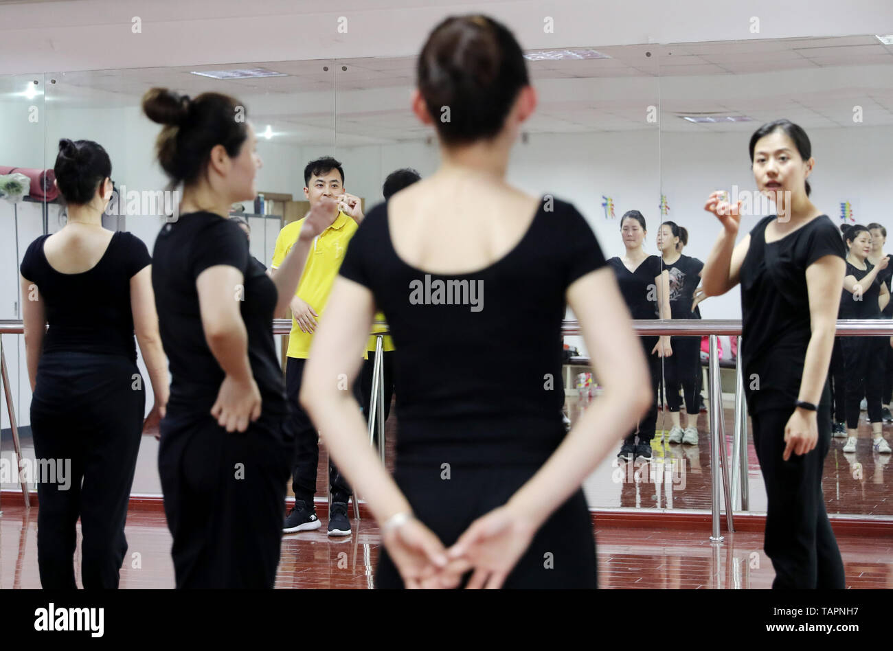 Shanghai, China's Shanghai. 26th May, 2019. Liu Jianqiang (3rd L), a teacher from the College of Dance of Shanghai Theatre Academy, conveys information through one of team members at a dance class for hearing-impaired people in Minhang District, east China's Shanghai, May 26, 2019. Gumeicaiyun in Minhang District is a dance group composed of people with hearing impairment. The 20-member team, aged between 20 and 40, is trained weekly by teachers from the college of dance of Shanghai Theatre Academy. Credit: Fang Zhe/Xinhua/Alamy Live News - Stock Image