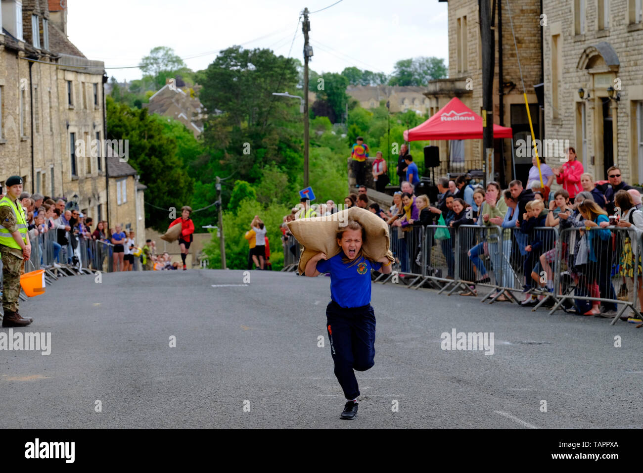 Tetbury, Gloucestershire, UK. 27th May, 2019. The annual races attract large crowds and raise money for local charities. Competitors race up steep Gumstool Hill in this pretty Cotswold town carrying a woolsack. The men carry a 60lb sack and the ladies a 30lb sack.This is the childrens race with a small sack. Credit: Mr Standfast/Alamy Live News - Stock Image