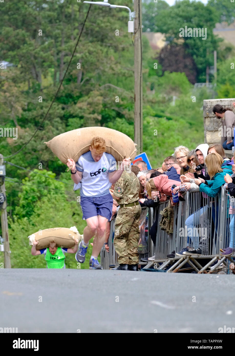 Tetbury, Gloucestershire, UK. 27th May, 2019. The annual races attract large crowds and raise money for local charities. Competitors race up steep Gumstool Hill in this pretty Cotswold town carrying a woolsack. The men carry a 60lb sack and the ladies a 30lb sack. Credit: Mr Standfast/Alamy Live News - Stock Image