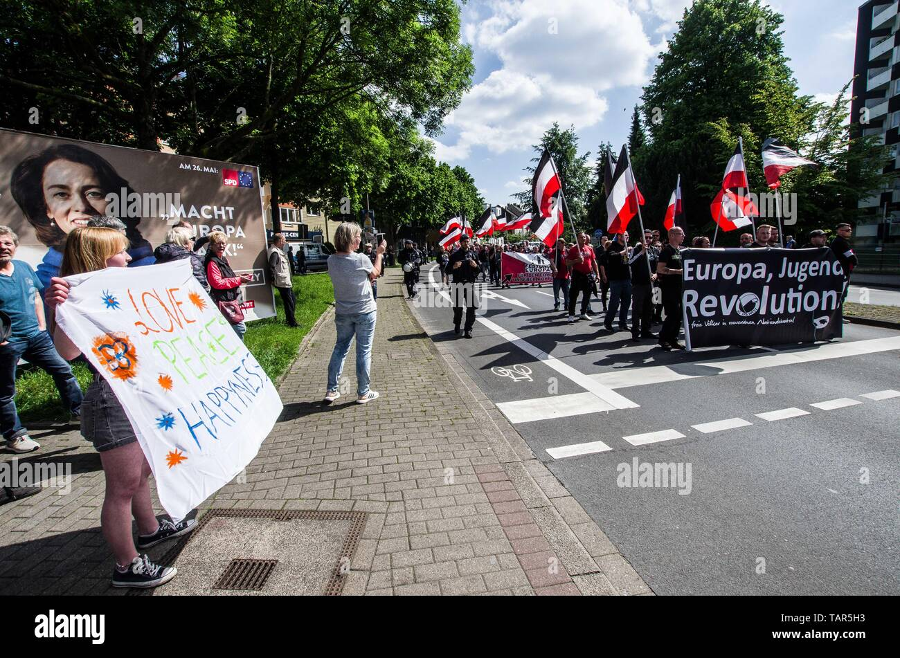 Dortmund, Nordrhein Westfalen, Germany. 25th May, 2019. A demonstrator against racism to the left of the approaching neonazi parade in Dortmund, Germany. Prior to the European Elections, the neonazi party Die Rechte (The Right) organized a rally in the German city of Dortmund to promote their candidate, the incarcerated Holocaust denier Ursula Haverbeck. The demonstration and march were organized by prominent local political figure and neonazi activist Michael Brueck (Michael Brück) who enlisted the help of not only German neonazis, but also assistance from Russian, Bulgarian, Hungarian, an Stock Photo