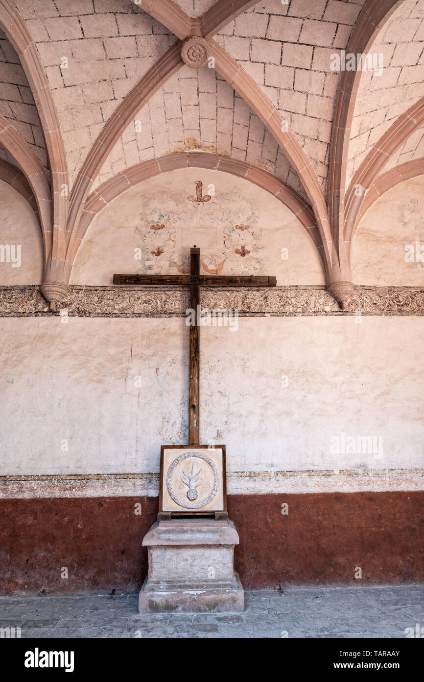 Wooden cross in the courtyard hall at the San Nicolas Tolentino Temple and Ex-Monastery in Actopan, Hidalgo, Mexico. The colonial church and convent  was built in 1546 and combine architectural elements from the romantic, gothic and renaissance periods. - Stock Image