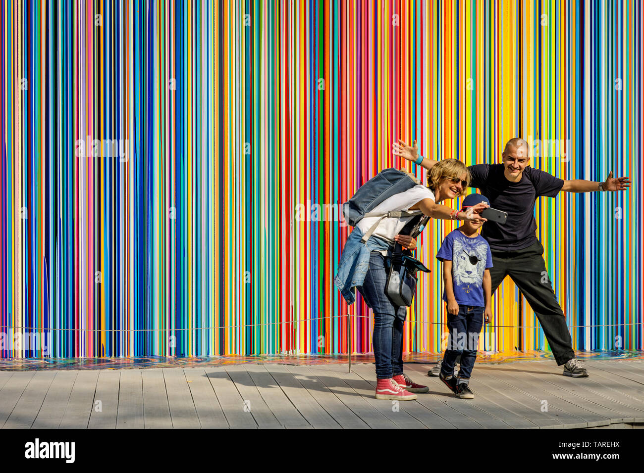 A family take a selfie portrait in front the art installation Giardini Colourfall by artist Ian Davenport at the 2017 Venice Biennale, Venice Italy. - Stock Image