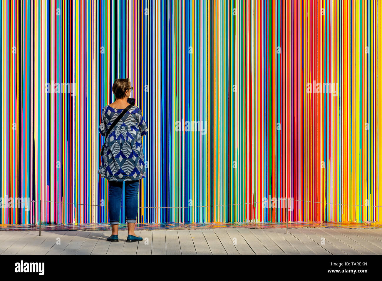 A tourist stands in front of Giardini Colourfall by artist Ian Davenport at the 2017 Venice Biennale, Venice Italy. - Stock Image