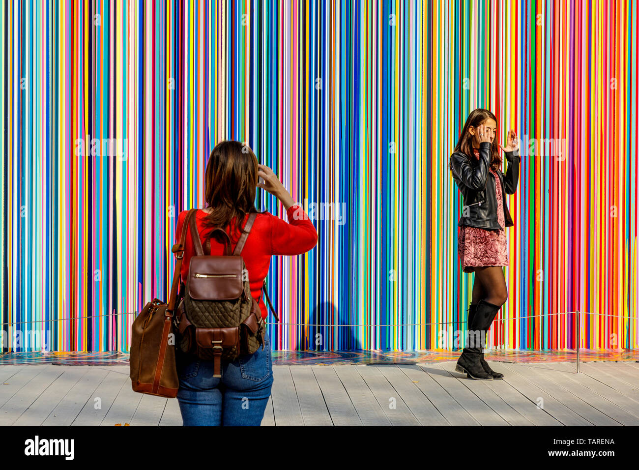 A young tourist poses for a photo in front the art installation Giardini Colourfall by artist Ian Davenport at the 2017 Venice Biennale, Venice Italy. - Stock Image