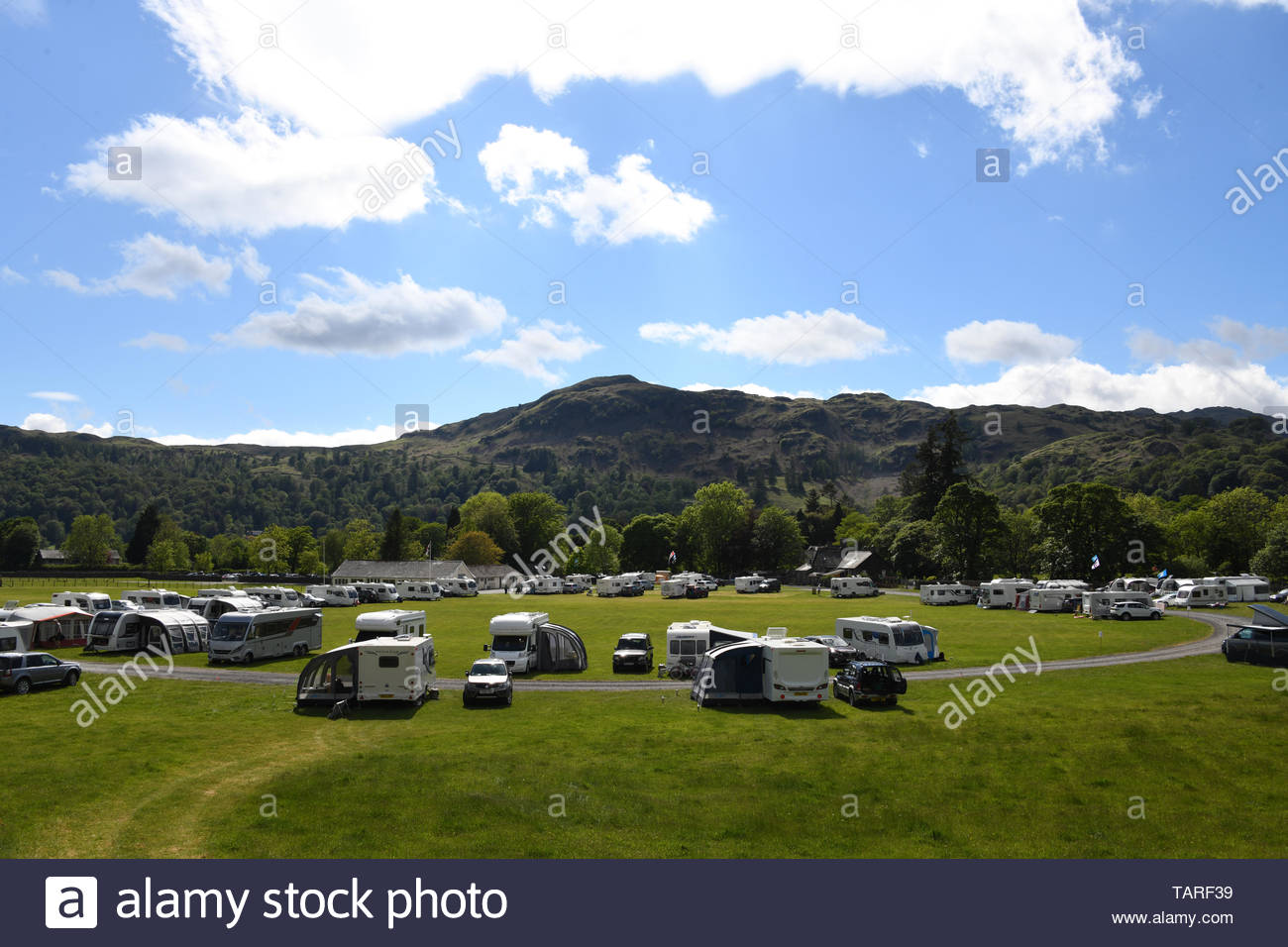 Dozens of caravans and campers parked up at Grasmere village in Cumbria in the Lake District for a camping holiday in the good sunny weather Stock Photo