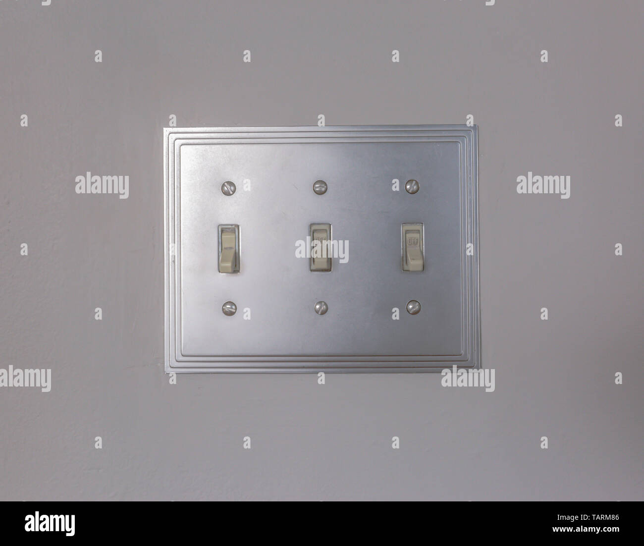 Close up view of vertical flip toggle light switches in off mode. The electrical light switches is mounted on the white wall inside a house. - Stock Image