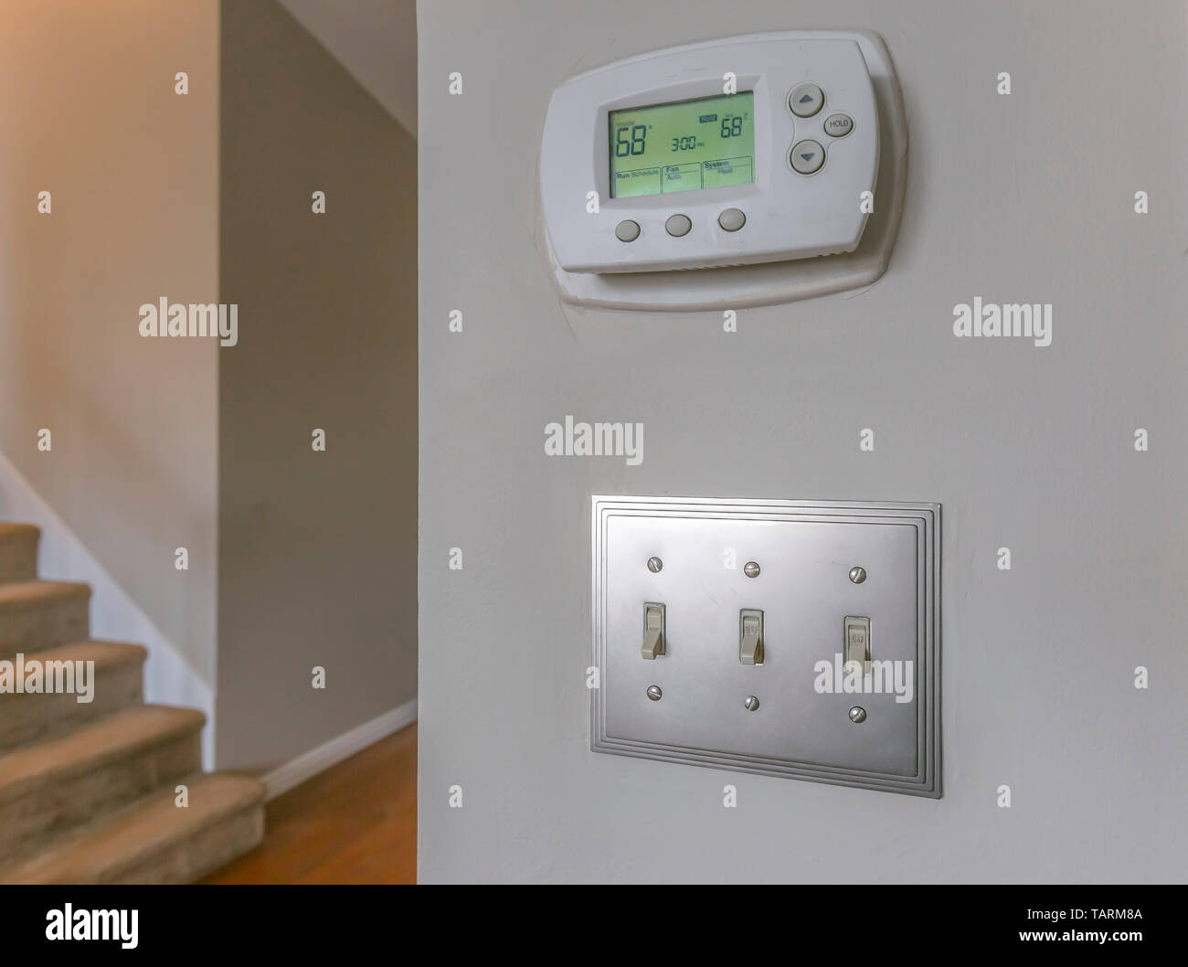 Wall mounted air conditioner unlit control and light switches inside a house. Carpeted stairs and hallway with wooden floor can be seen in the backgro - Stock Image