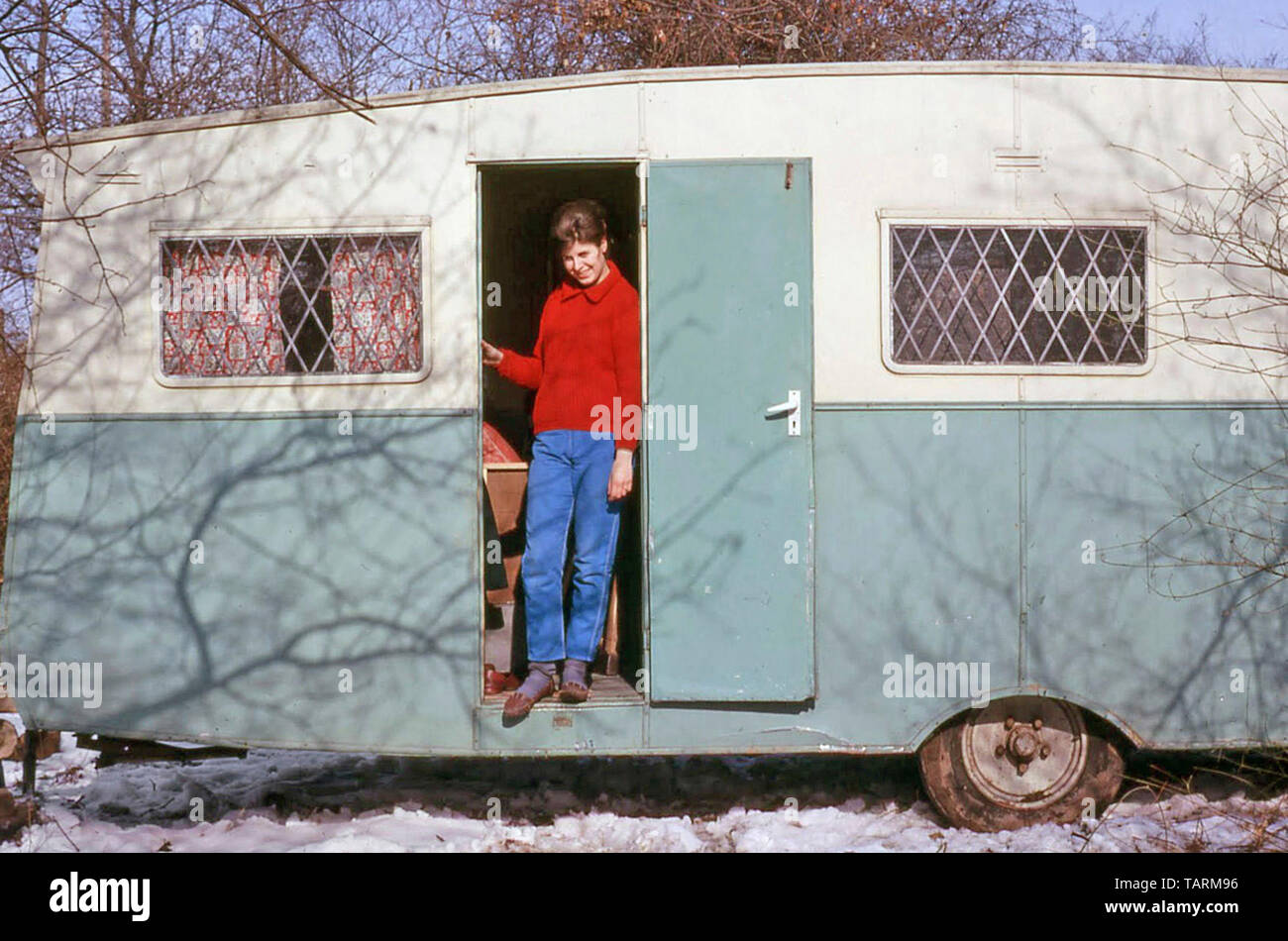 Archival 1960s just married young woman standing in doorway of dilapidated old caravan snow covered building site first marital home 60s England UK Stock Photo