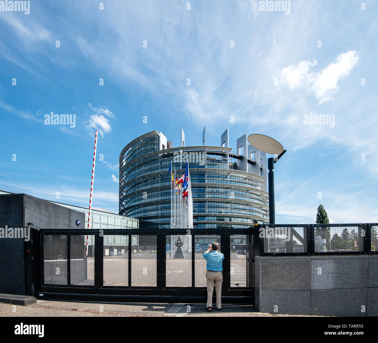 Strasbourg, France - May 26, 2019: Seniopr man taking photograph through the closed gate of the European Parliament headquarter with all European Union flags waving - clear blue sky in background - Stock Image