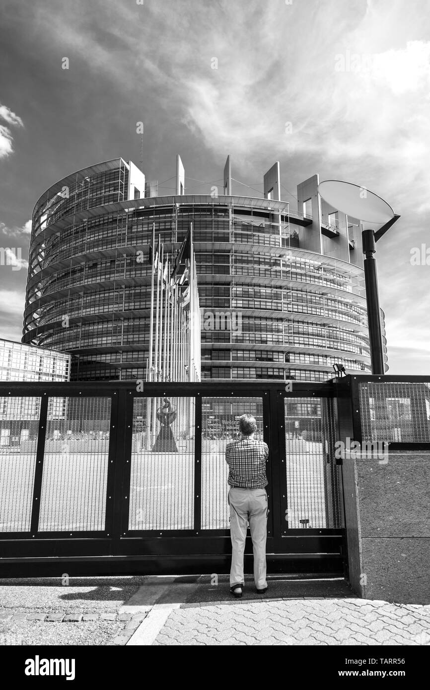 Strasbourg, France - May 26, 2019: Seniopr man taking photograph through the closed gate of the European Parliament headquarter with all European Union flags waving - black and white - Stock Image