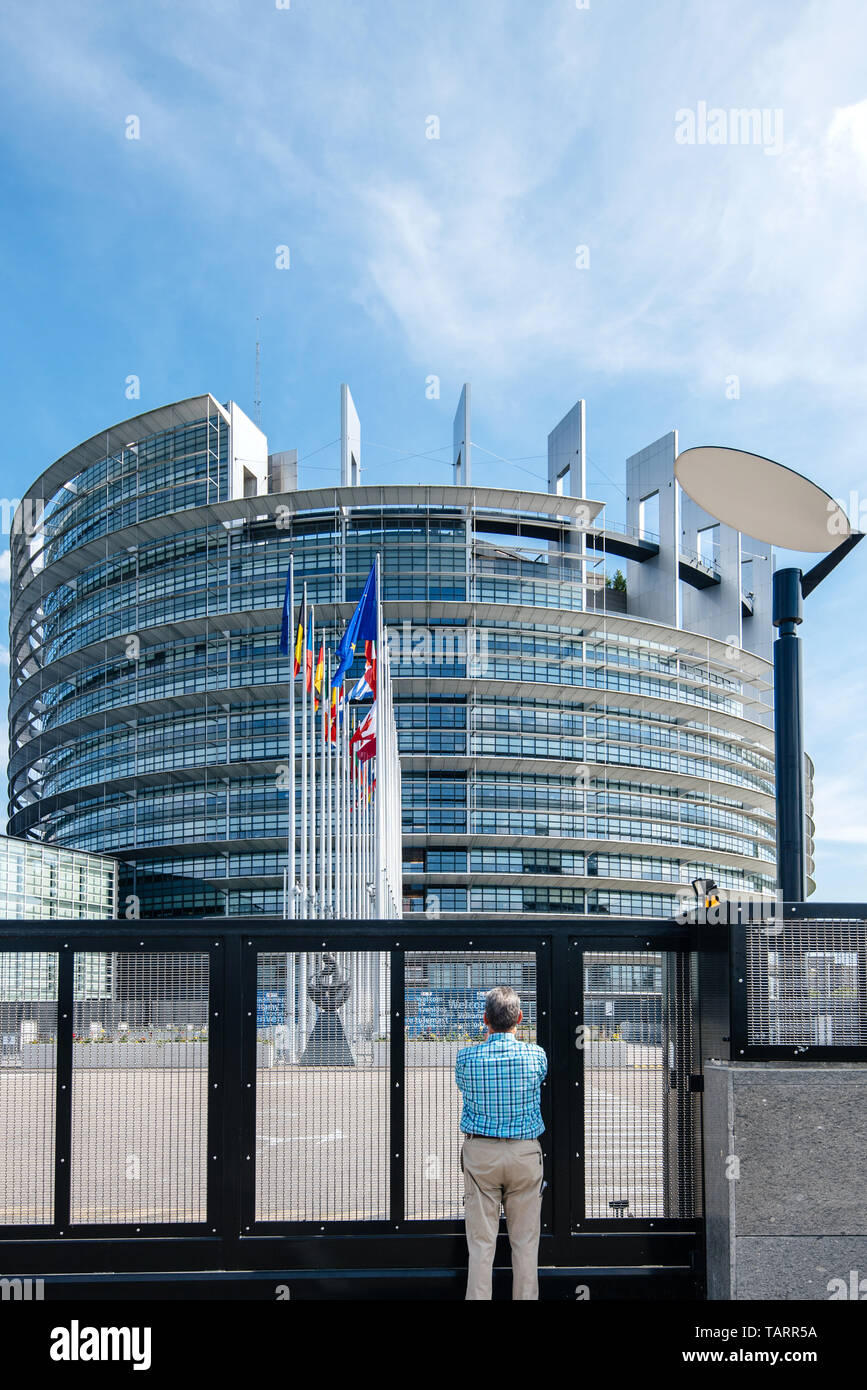Strasbourg, France - May 26, 2019: Seniopr man admiring through the closed gate of the European Parliament headquarter with all European Union flags waving - clear blue sky in background - Stock Image