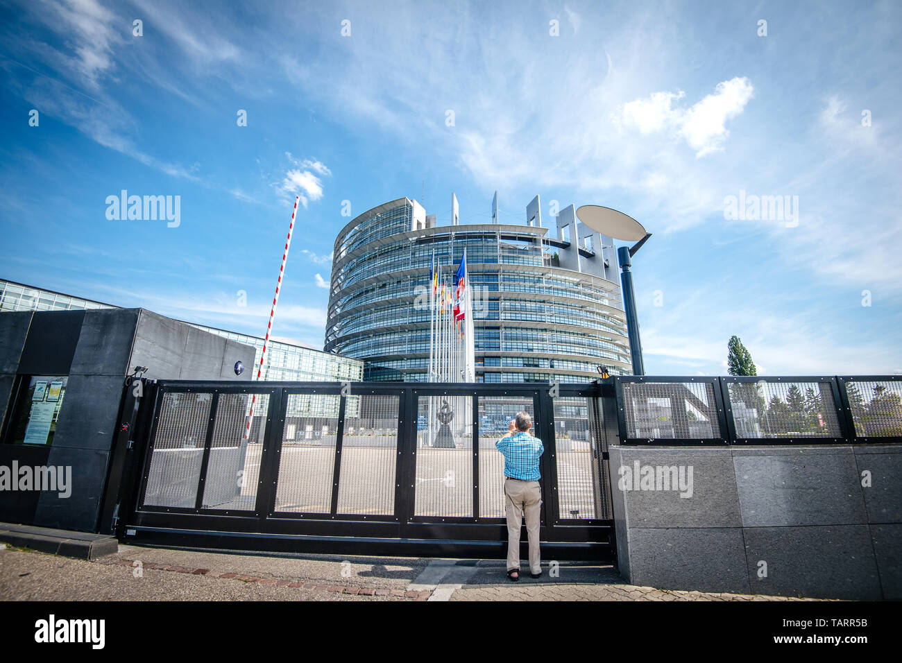 Strasbourg, France - May 26, 2019: Seniopr man taking photograph through the closed gate of the European Parliament headquarter with all European Union flags waving - clear blue sky in background horizontal image - Stock Image