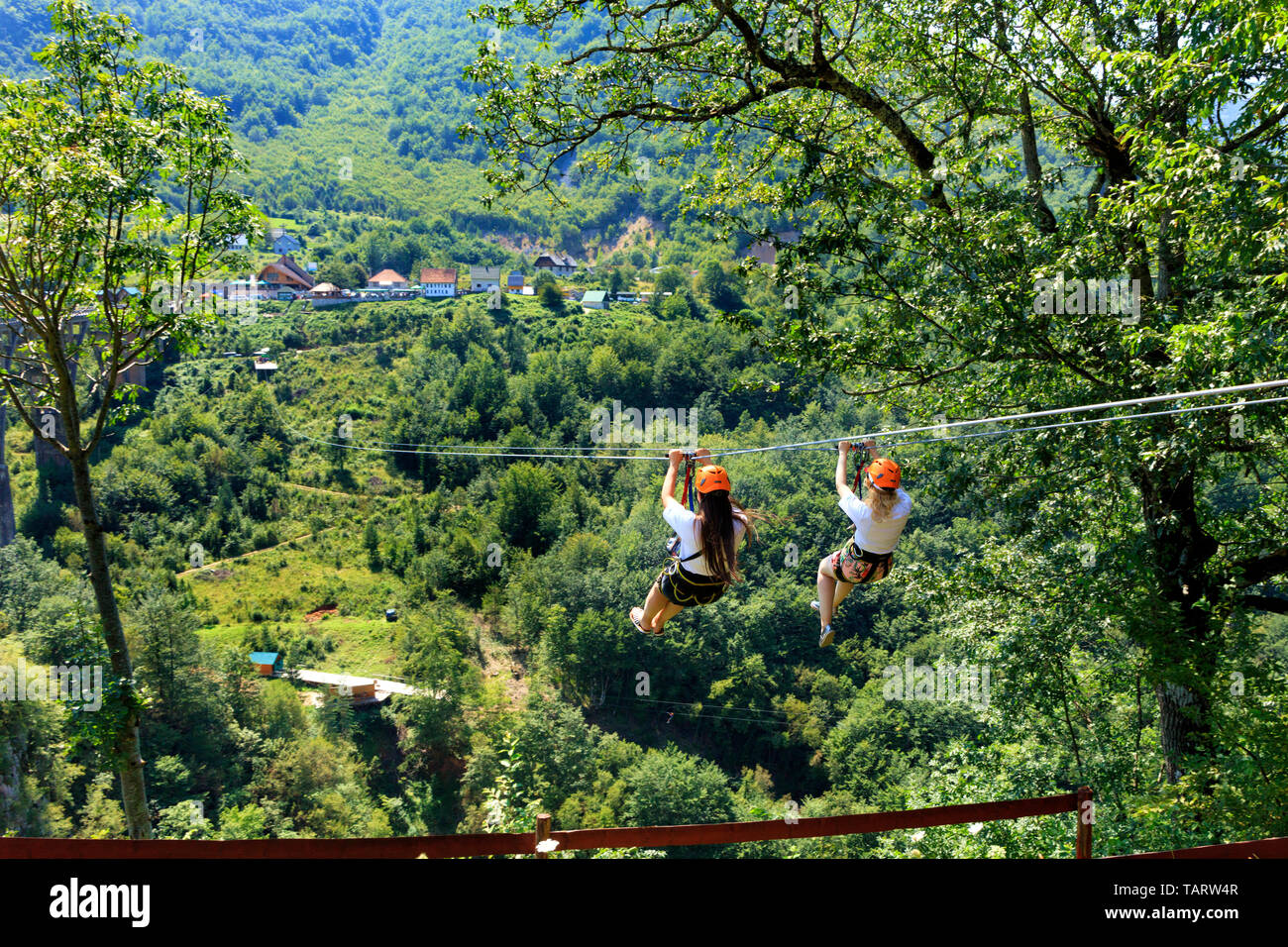 Girls on the cable car are sent through the mountain and the forest through the valley of the river Tiara in Montenegro. - Stock Image