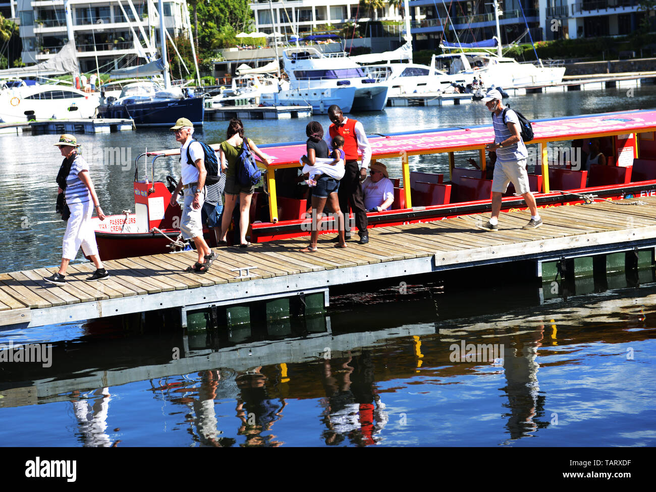 Tourist getting off the harbour tour boat in the marina by the V&A waterfront in Cape Town. - Stock Image