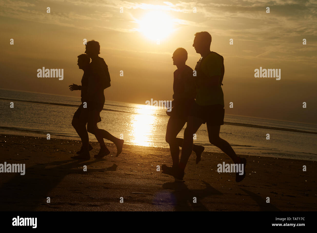 Silhouette of a group of adults enjoying a run along the beach in golden light during sunset - Stock Image
