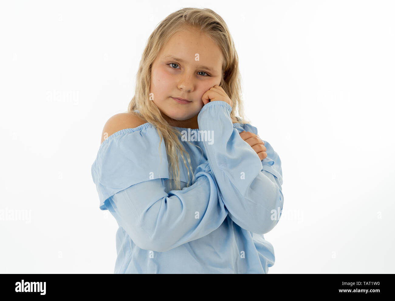 Close up portrait of a cute young shy girl looking timid at the camera on a white background. In facial expression photo concept - Stock Image