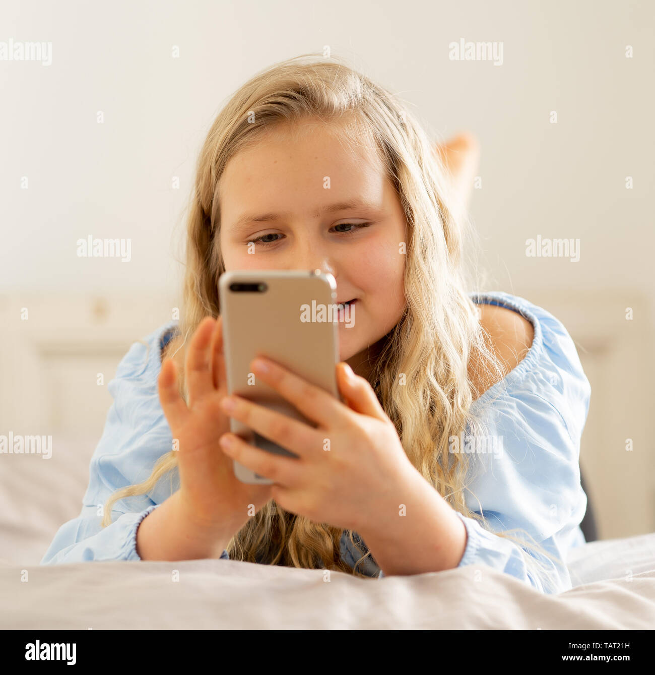 Beautiful blonde happy little girl playing on mobile phone. Cute child chatting on the internet with smartphone social media app lying in bed at home. - Stock Image