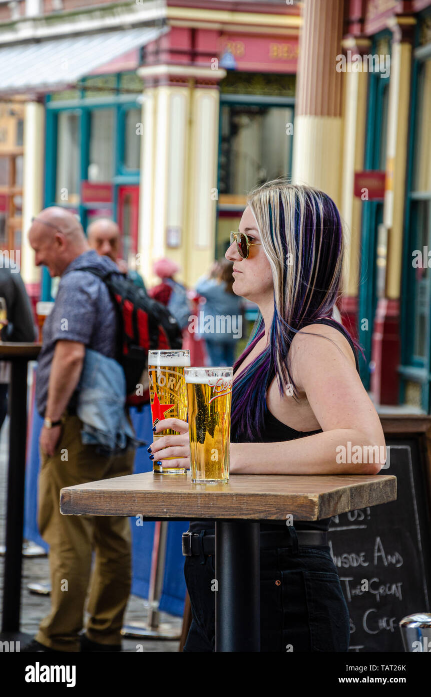 A lady poses for a portrait outside The Lamb Tavern in The Leadenhall Market in the financial district of The City of London, UK - Stock Image