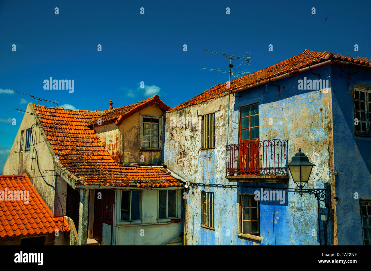 Old colorful houses with worn plaster in a sunny day at Seia. A nice village of Portugal also known for its delicious cheese. - Stock Image