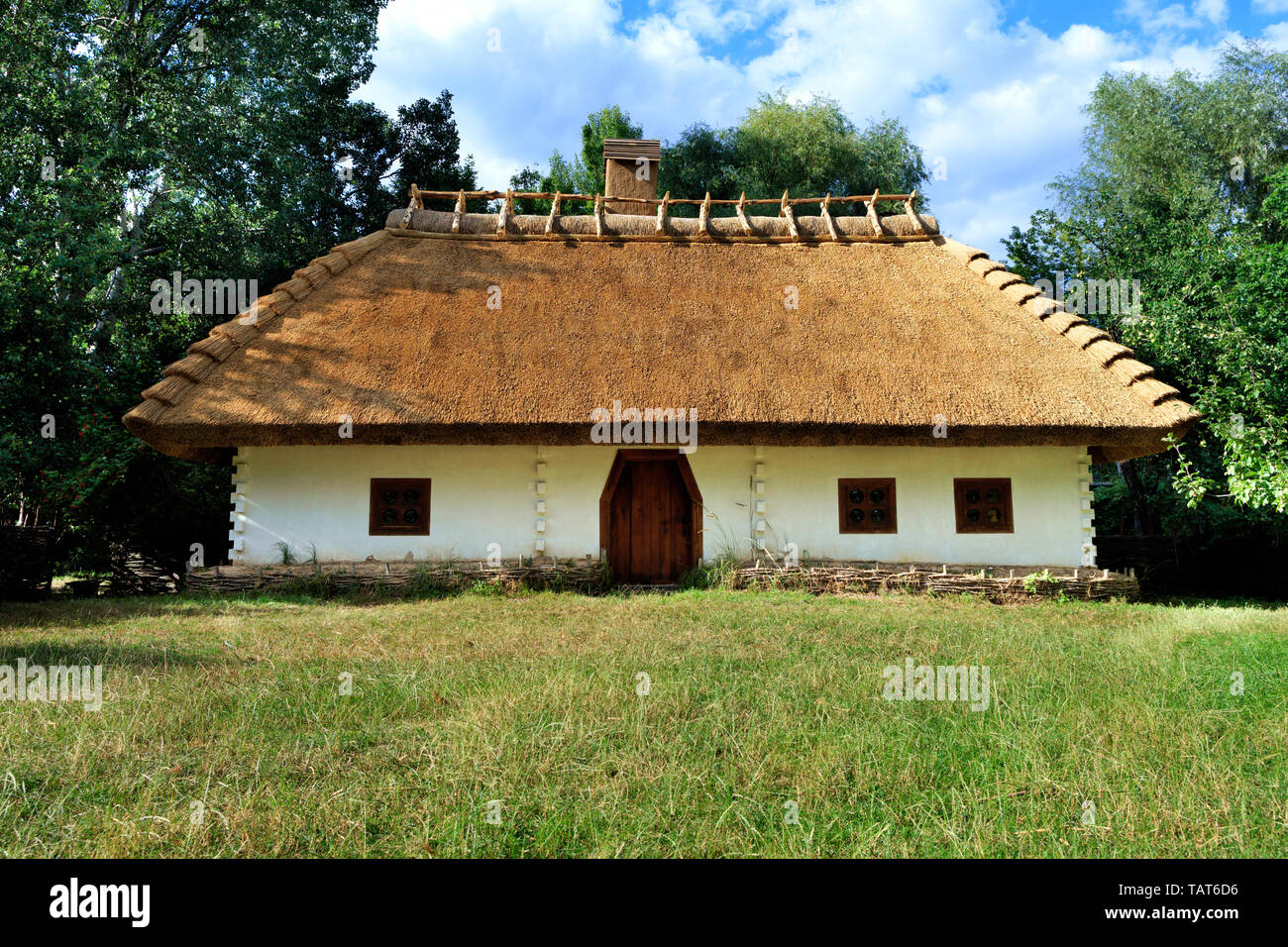 Old traditional Ukrainian rural house with a thatched roof and a wicker fence in the garden with green grass and copy space against a blue sky with a  Stock Photo